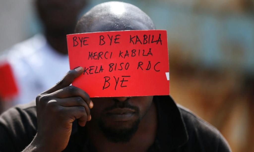 Un homme tient une pancarte avec un message pour le président Kabila lors de manifestations à Kinshasa lundi. Photographie : Thomas Mukoya /Reuters