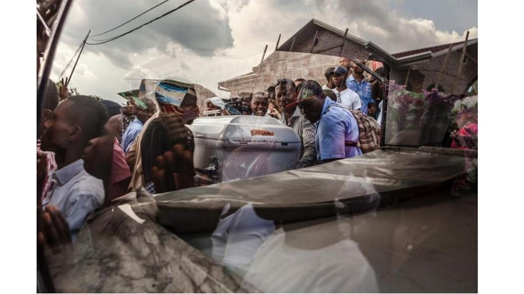 Une photo prise à travers une fenêtre montre les partisans du parti d'opposition UDPS portant le cercueil d'un militant à Kinshasa, le 31 octobre 2016, après les corps de six autres du parti d'opposition congolaise, qui ont été brûlés dans des incendies criminels dans la nuit du 19 septembre 2016 au siège de la partie, ont été libérés de la morgue