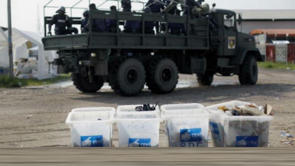 Des militaires passent près d'urnes électorales transformées en poubelles, après les élections de décembre 2011. © Jerome Delay/AP/SIPA
