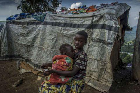 Une jeune fille déplacées congolaise  épluche les légumes tout en prenant soin de sa sœur dans le Nord-Kivu, en RDC.