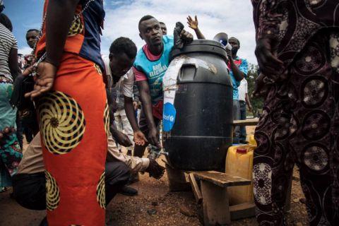 Plusieurs personnes font la queue pour se laver les mains à l'eau chlorée destinée à prévenir la propagation du virus Ebola dans un bureau de vote emblématique de Beni, en République démocratique du Congo, le 30 décembre 2018.